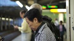 Senior Asian couple taking train transportation together Stock Footage