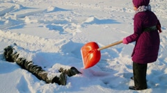 Young boy and girl play with spade in snow at winter day Stock Footage