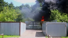Fire flames and black smoke goes from plants near garages at sunny day Stock Footage