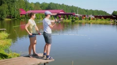 Mother and her son fishing on small pier near pond Stock Footage