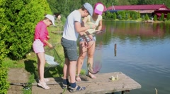 Mother and two her children look their yield on small pier near pond Stock Footage