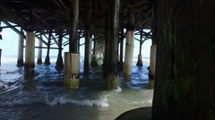 Underneath a pier on a beach during the day Stock Footage