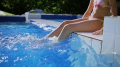 Young girl in swimsuit sit on pool border and splatters at sunny day Stock Footage