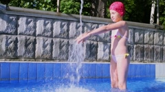 Young girl in swimsuit stands near water jet and splatters at sunny day Stock Footage