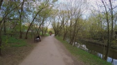 Bicycle ride by alley in park near Jauza river at spring day Stock Footage