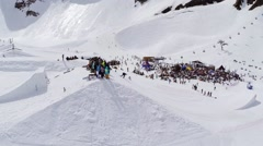 Quadrocopter shoot snowboarder ride on springboard. Ski resort. Crowds of people Stock Footage