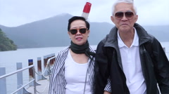 Stylish Asian senior walking together at lake cruise ship pier Stock Footage