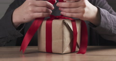 Teen girl hands tying ribbon bow on present box Stock Footage