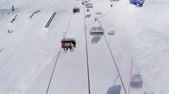 Quadrocopter shoot snowboarders and skiers in ski lifts. Ski resort. Sunny day Stock Footage