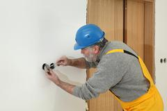 Electrician at construction site install electrical plug Stock Photos