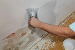 Worker spreading plaster to damaged wall Stock Photos