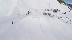 Quadrocopter fly above springboards on ski resort. People ride. Sunny day Stock Footage