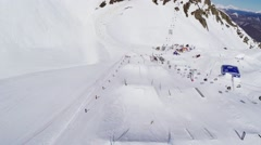 Quadrocopter fly above springboards on ski resort. Landscape. Riders. Sunny Stock Footage