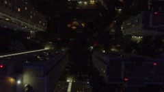 Cars ride by roads among tall houses at spring night. Aerial view Stock Footage