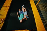 Couple lie on trampoline in the park Stock Photos