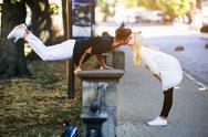 Man performs an acrobatic trick near a girl Stock Photos
