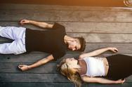 Couple lying together on the hardwood floor Stock Photos