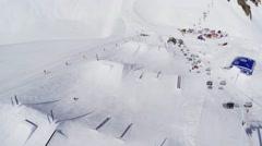 Quadrocopter shoot riders on springboards on ski resort. Ski lifts. Landscape Stock Footage
