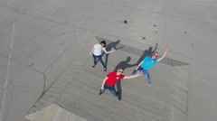 Three young people synchronous dance on square at sunny day Stock Footage