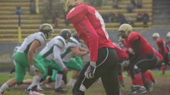 Strong football players pushing rivals in fight for ball on scrimmage line Stock Footage