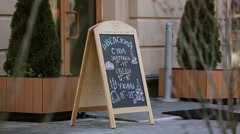 Handwritten street menu on blackboard in front door of restaurant. Cafe. Dinner Arkistovideo