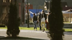 Group of young people slowly walk on street. Sunny evening. Spruce trees Stock Footage