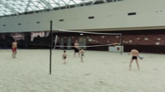 Men play volleyball with kids on artificial sand beach under roof of building Stock Footage