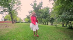 Happy woman in a red jacket on sunny day Stock Footage