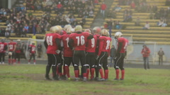 Gridiron football team standing in circle, discussing game strategy in field Stock Footage