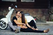 Cute couple with their scooter in the city Stock Photos