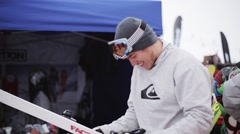 Happy skier fixing ski by screwdriver on ski resort. Smile in camera. Holidays Stock Footage