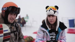 Young man and woman drink coffee in encamp on ski resort. Smile in camera Stock Footage