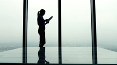 Silhouette of businesswoman reading documents standing by window in office Stock Footage