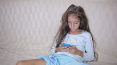 Girl child with a cell phone browses the Internet Stock Footage