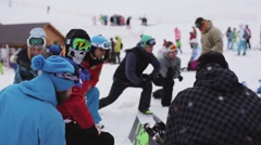 Group of snowboarders warm up before riding on ski resort. Make exercises Stock Footage