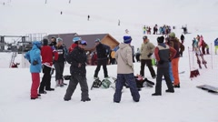 Group of snowboarders warm up before riding on ski resort. Make exercises. Snow Stock Footage