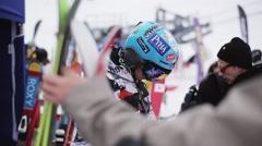 Snowboarder in helmet check ski in encamp on ski resort. Mountains. People Stock Footage