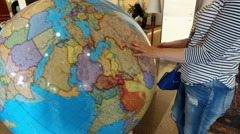 Visitors to the hotel turns the large globe Stock Footage
