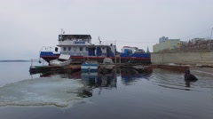 Vessels on moorage at river with ice and diver swim Stock Footage