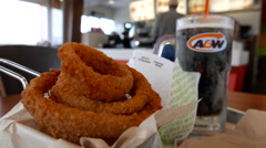 Motion of onion rings and root beer on table at A&W restaurant Stock Footage