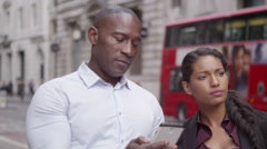 4k Attractive mixed ethnicity couple on city street using phone for navigation Stock Footage