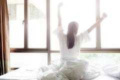 Woman stretching in bed after wake up. Stock Photos