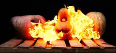 Two Halloween pumpkins on the boards against each other spew flames fire on t Stock Photos