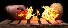 Two Halloween pumpkins on the boards against each other spew flames fire on a Stock Photos