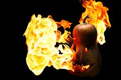 Scary Halloween pumpkin is spewing fire flame isolated on black background Stock Photos
