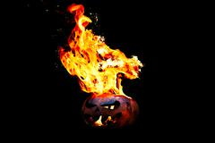 Halloween pumpkin on fire isolated on a black background Stock Photos