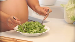 Pregnant woman mixing salad in a bowl in the kitchen. Stock Footage