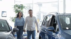 Couple comes to the blue SUV at the dealership Stock Footage