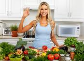 Happy woman cooking in the kitchen. Stock Photos