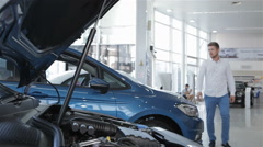 Man looks at the engine compartment of the car at the dealership Stock Footage